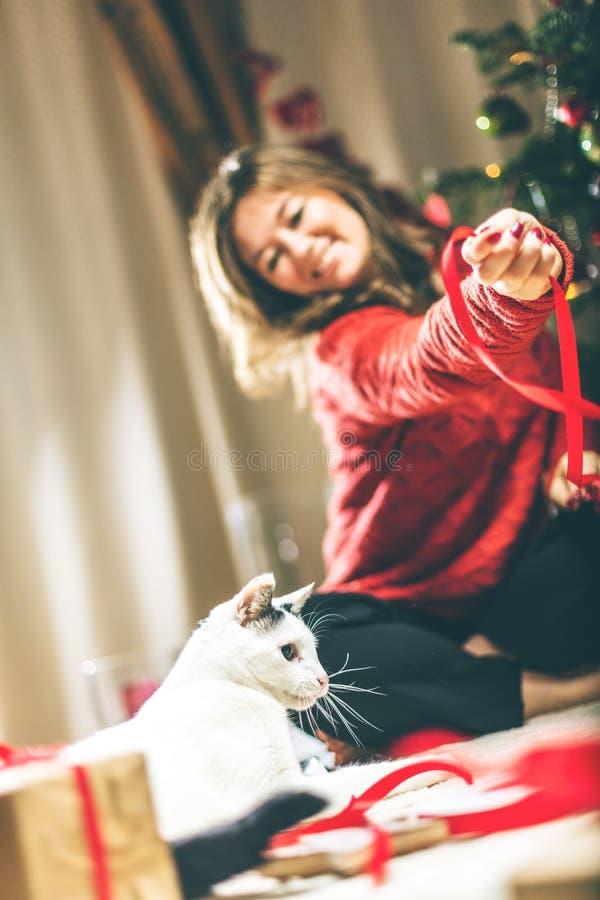 Vrouw die en Kerstmis Huidig met kleine kat verpakken verfraaien stock foto's