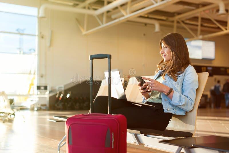Vrouw die en laptop texting met behulp van alvorens op het vliegtuig te krijgen royalty-vrije stock afbeelding
