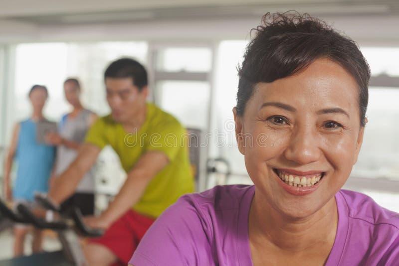 Vrouw die en op de hometrainer bij de gymnastiek glimlachen uitoefenen, die camera bekijken stock afbeelding