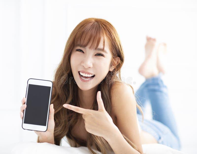 vrouw die en smartphone glimlachen tonen terwijl het liggen op het bed royalty-vrije stock foto