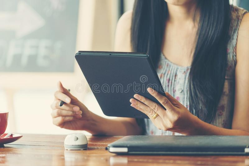 Vrouw die en tablet in koffiewinkel werken gebruiken stock afbeeldingen