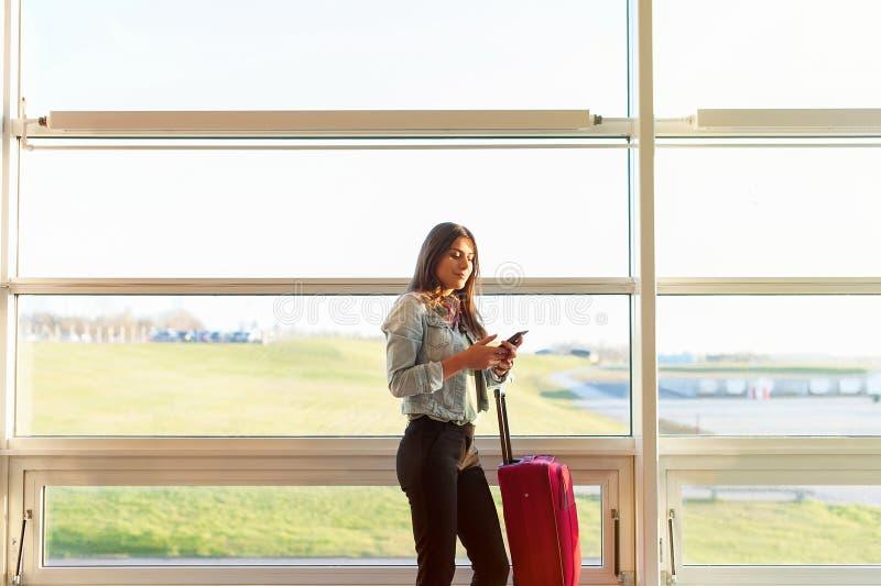 Vrouw die en telefoon texting met behulp van alvorens op het vliegtuig te krijgen stock fotografie