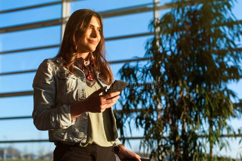 Vrouw die en telefoon texting met behulp van alvorens op het vliegtuig te krijgen stock foto's