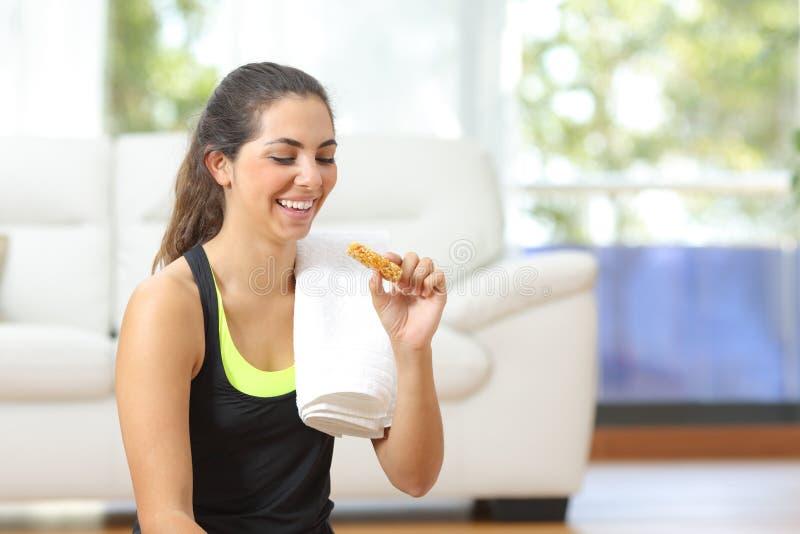 Vrouw die energiebar na sport thuis eet royalty-vrije stock foto's