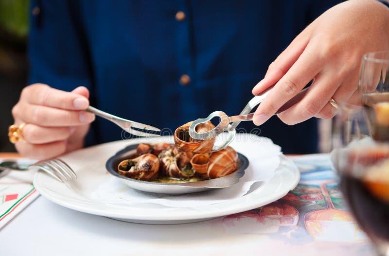 Vrouw die escargot met speciale vork en tang eet royalty-vrije stock afbeelding