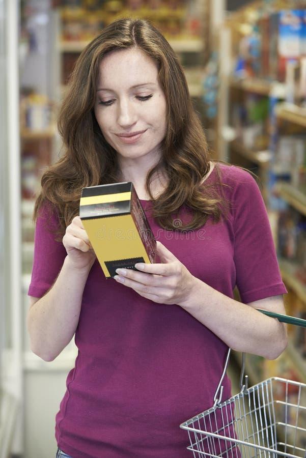 Vrouw die Etikettering controleren op Doos in Supermarkt royalty-vrije stock foto's