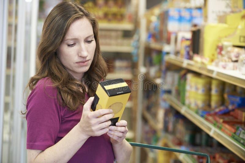 Vrouw die Etikettering controleren op Doos in Supermarkt royalty-vrije stock foto