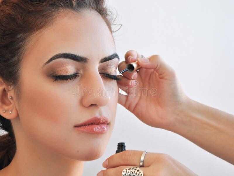 Vrouw die eyeliner op haar ogen toepassen royalty-vrije stock afbeeldingen