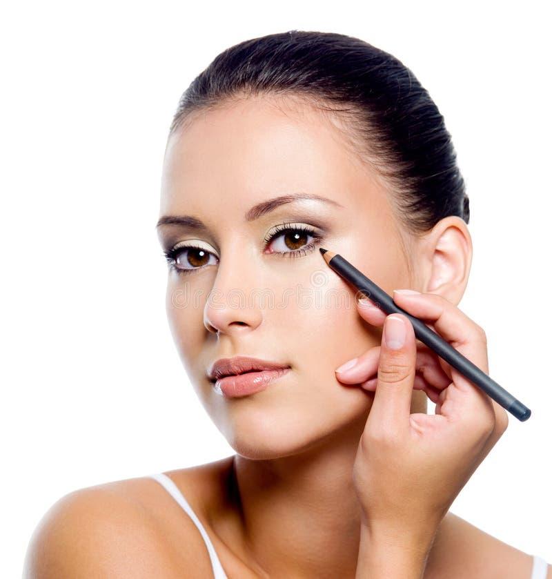 Vrouw die eyeliner op ooglid met pensil toepast stock afbeelding