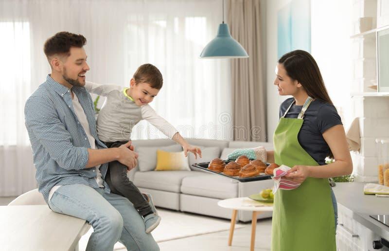 Vrouw die familie behandelen met oven gebakken broodjes stock afbeeldingen