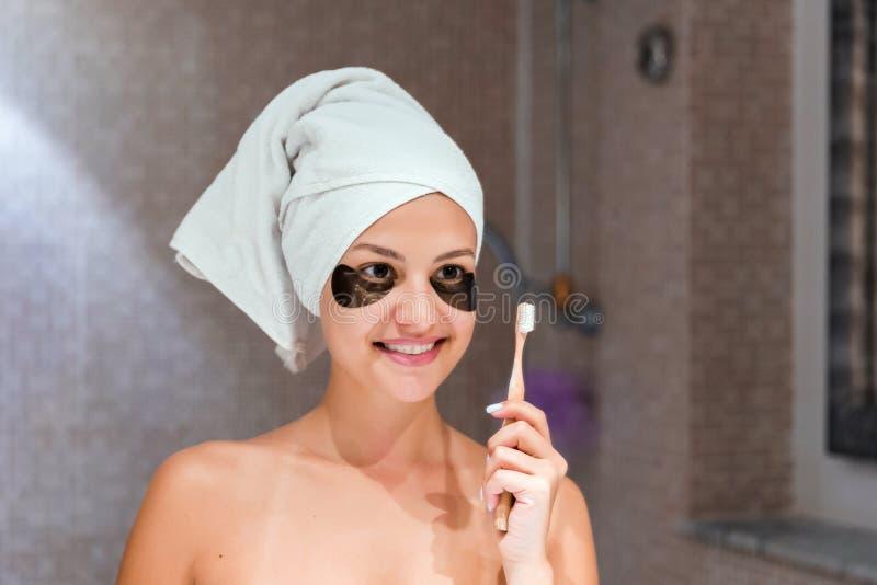 Vrouw die in flarden haar tanden in de badkamers in de ochtend borstelt Healty skincare en wellnessconcept royalty-vrije stock fotografie