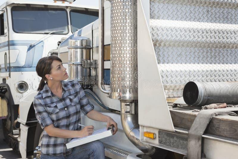 Vrouw die flatbed vrachtwagen inspecteren royalty-vrije stock fotografie