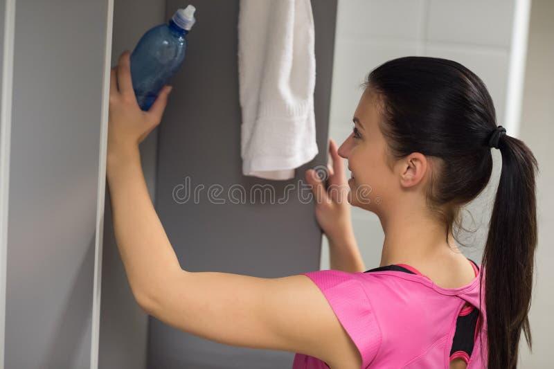 Vrouw die fles in kast zetten bij gymnastiek royalty-vrije stock afbeelding