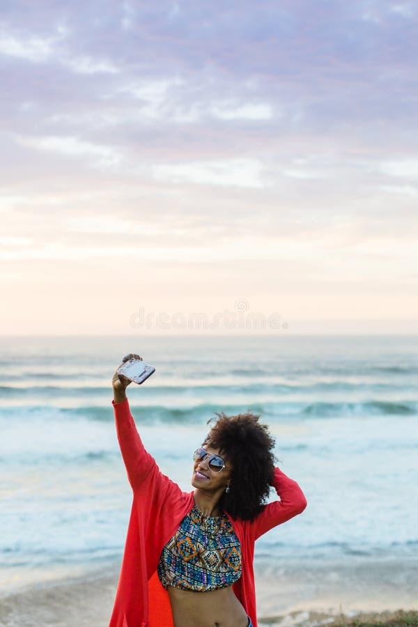 Vrouw die foto met mobiele telefoon nemen tegen het overzees stock afbeeldingen