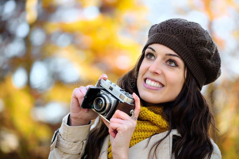 Vrouw die foto met retro camera in de herfst nemen royalty-vrije stock afbeeldingen