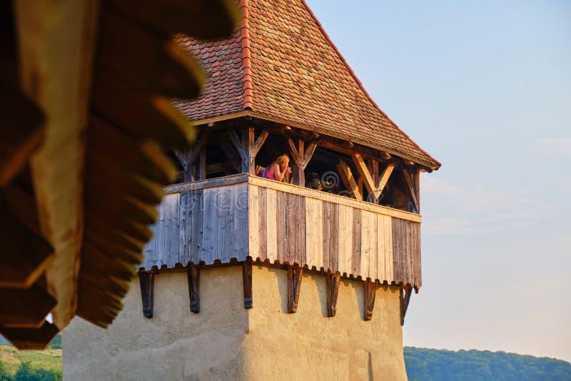 Vrouw die foto's in een toren, in de versterkte Evangelische kerk van Alma Vii, Transsylvanië, Roemenië, met het warme zon plaats royalty-vrije stock foto