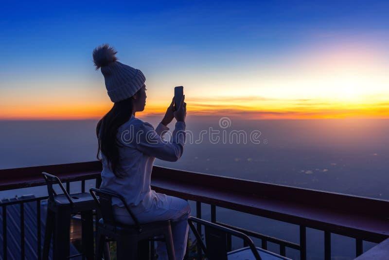 Vrouw die foto's van zonsopgang nemen royalty-vrije stock afbeelding
