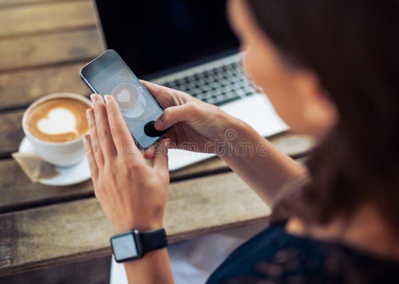 Vrouw die foto van koffie met smartphone nemen royalty-vrije stock fotografie