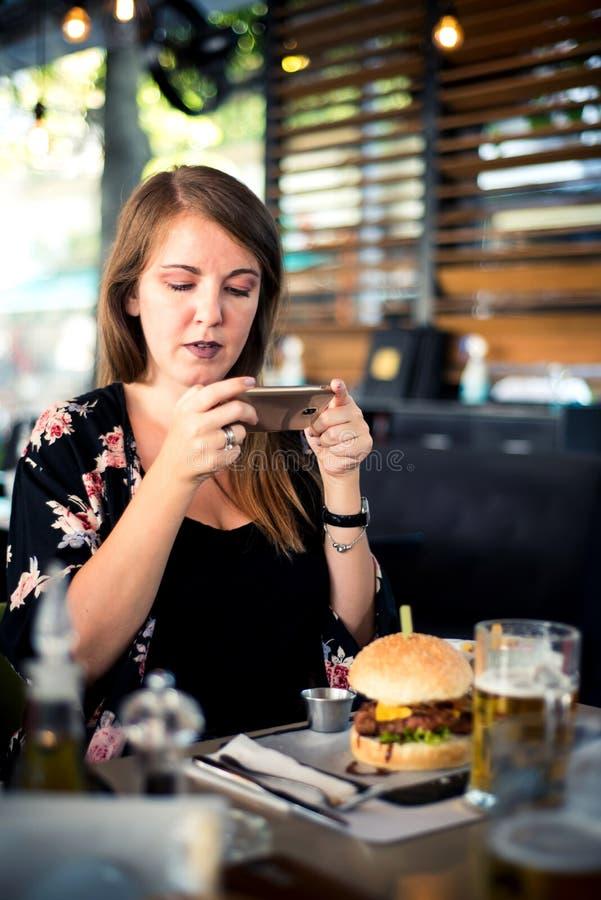 Vrouw die foto van voedsel nemen bij het restaurant stock fotografie