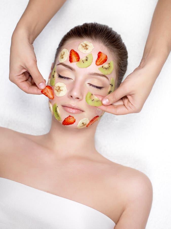 Vrouw die fruit kosmetisch gezichtsmasker krijgt stock foto