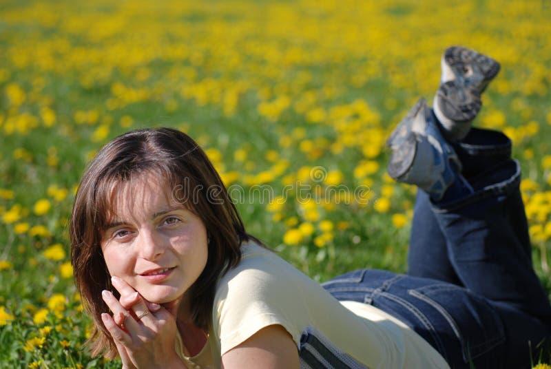 Vrouw die in gebied van bloemen ligt royalty-vrije stock afbeelding