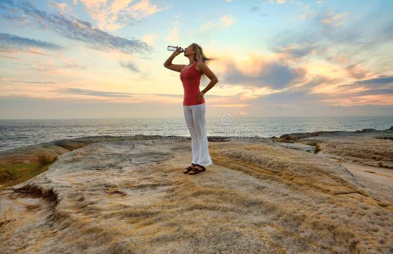 Vrouw die gebotteld water in openlucht drinken royalty-vrije stock foto's