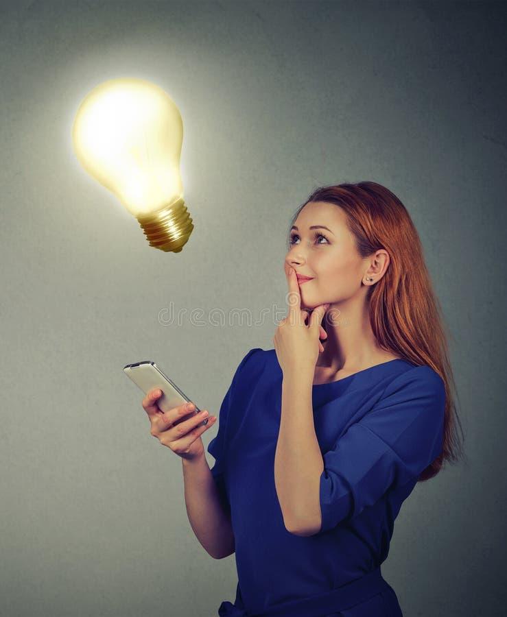Vrouw die gebruikend mobiele telefoon die omhoog gloeilamp bekijken texting Het concept van het technologieidee royalty-vrije stock foto