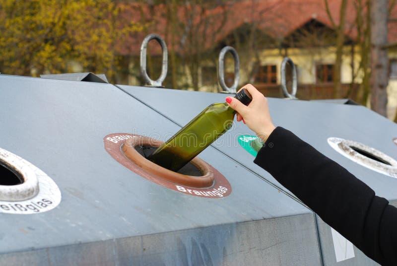Vrouw die gebruikte glas brengen aan de flessenbank stock afbeeldingen