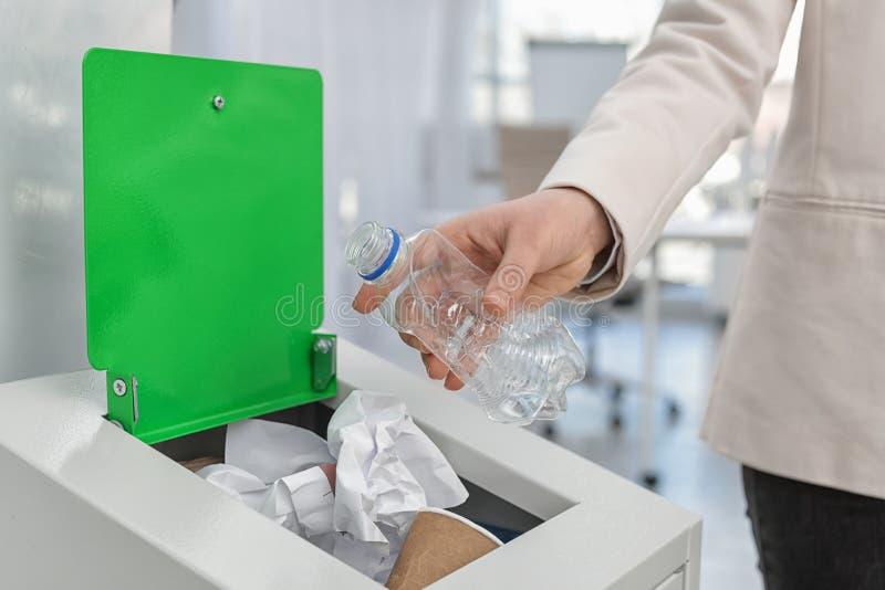 Vrouw die gebruikte plastic fles zetten in afvalbak in bureau, close-up Het recycling van het afval royalty-vrije stock foto