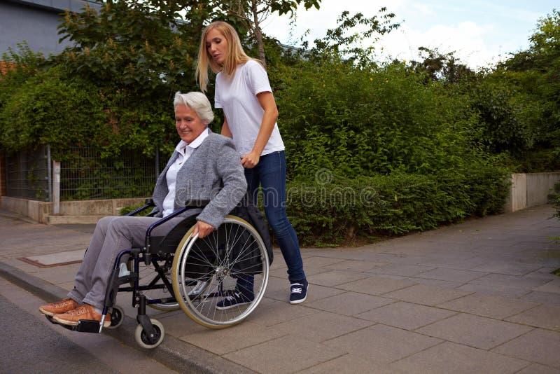 Vrouw die gehandicapte persoon helpt stock afbeeldingen