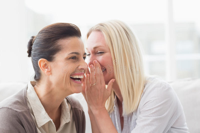 Vrouw die geheim openbaren aan haar vriend het glimlachen stock afbeeldingen