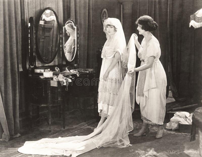 Vrouw die gekleed bruid helpen worden royalty-vrije stock foto's