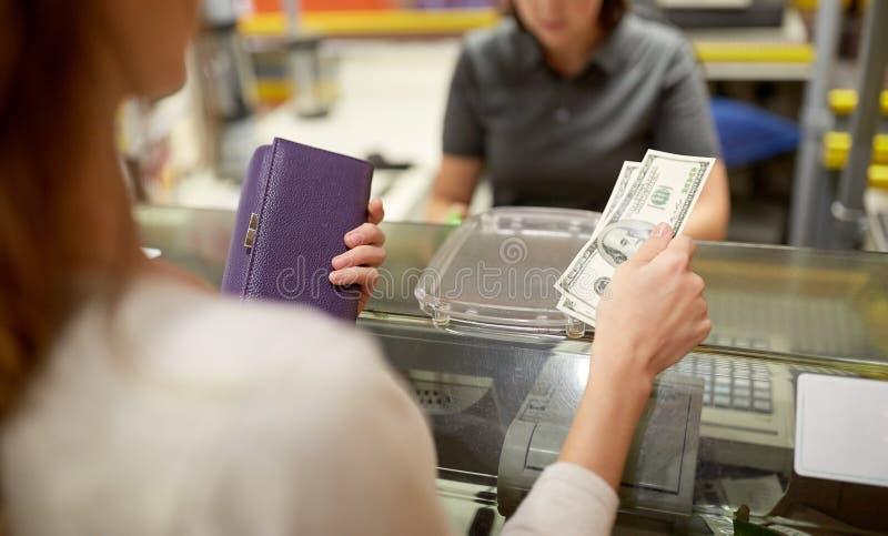 Vrouw die geld betalen bij opslagkasregister royalty-vrije stock foto's