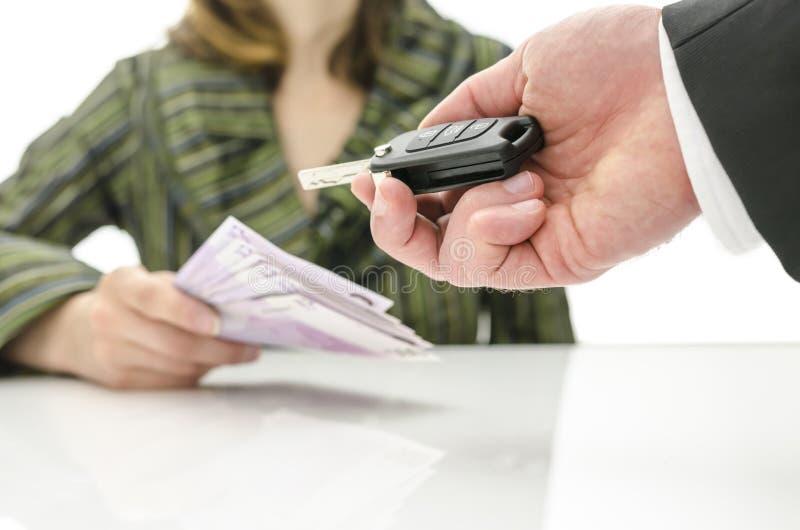 Vrouw die geld in ruil voor autosleutel geven royalty-vrije stock afbeelding