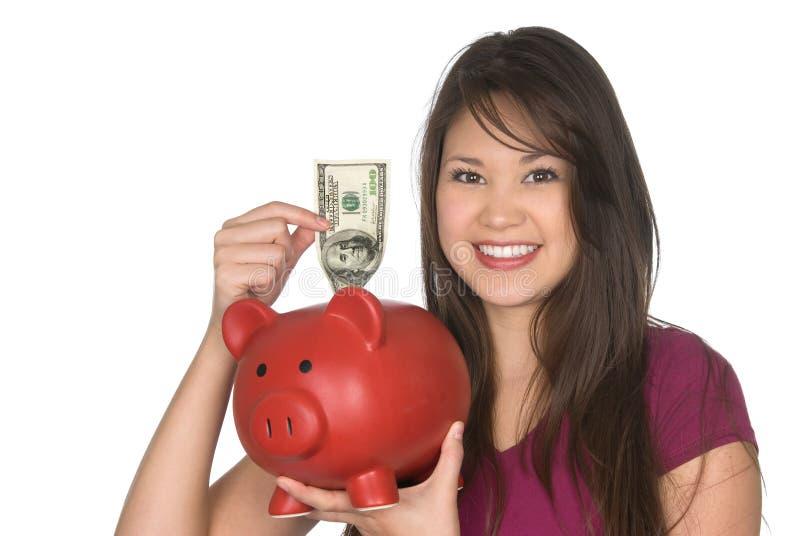 Vrouw die geld in spaarvarken zet royalty-vrije stock afbeelding