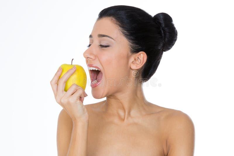 Vrouw die gele appel eet stock foto's