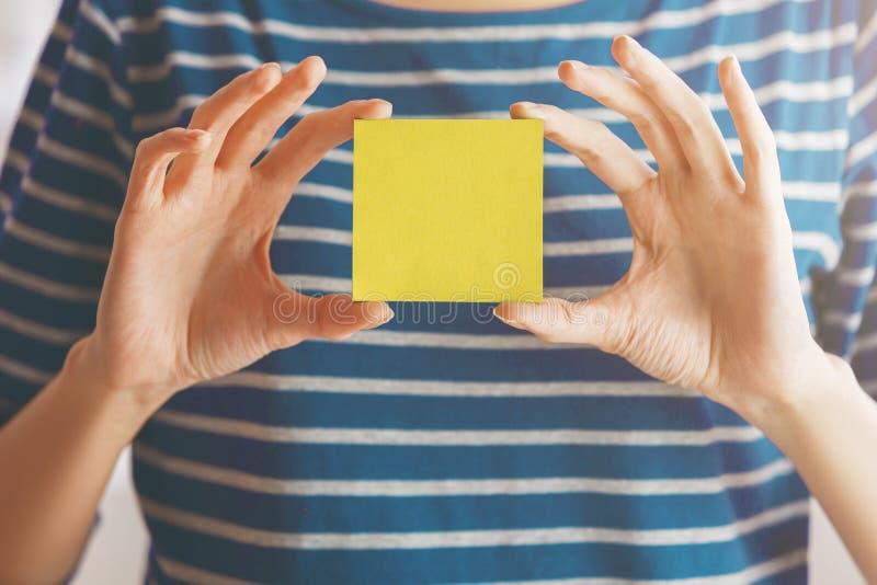 Vrouw die gele sticker houden stock afbeelding