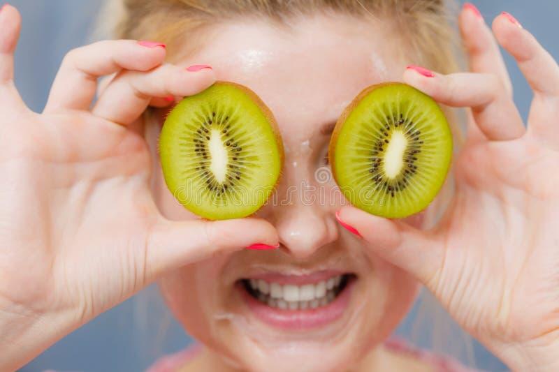 Vrouw die gelmasker op de kiwi van de gezichtsholding hebben royalty-vrije stock afbeeldingen