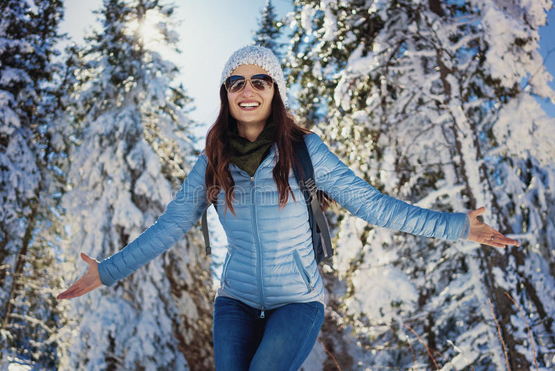Vrouw die gelukkige de wintergang in sneeuw behandeld hout hebben stock afbeelding
