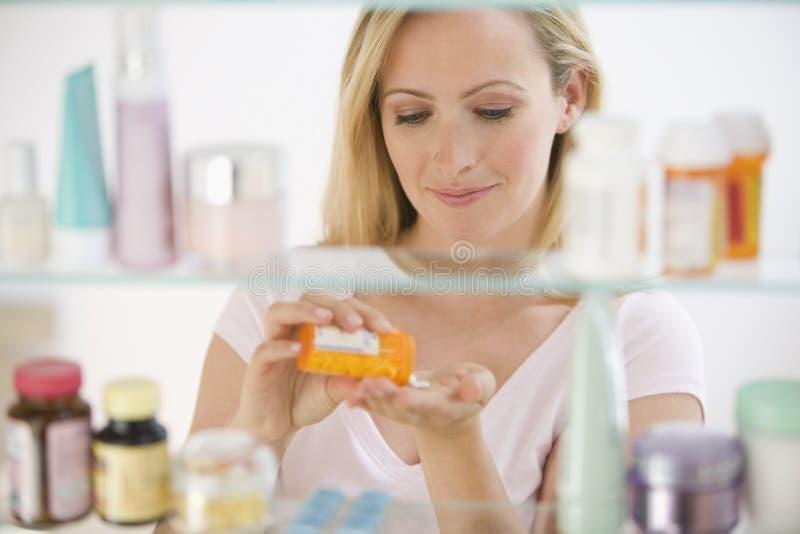 Vrouw die Geneeskunde krijgt stock foto