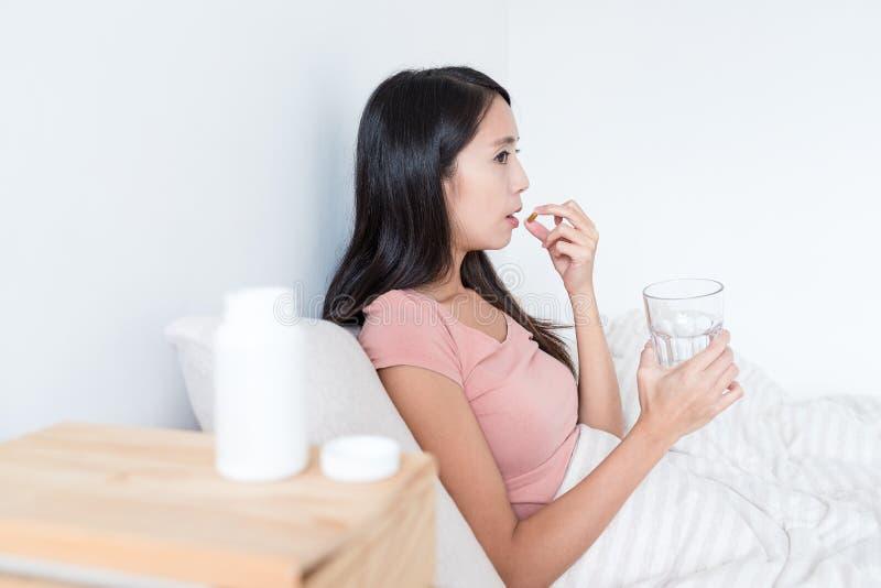 Vrouw die geneeskunde nemen en glas water op bed houden stock afbeeldingen