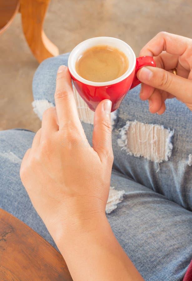 Vrouw die in gescheurde jeans bij koffiewinkel zitten royalty-vrije stock foto
