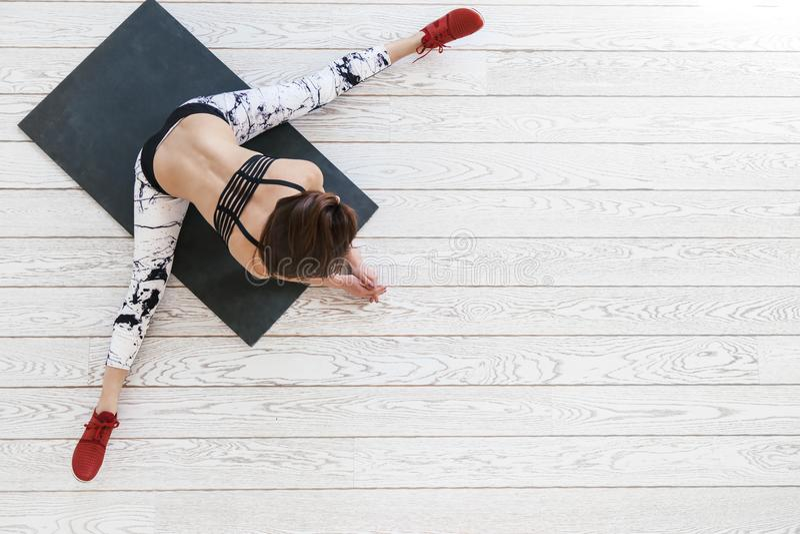 Vrouw die geschikte oefening op witte bevloering doen stock fotografie