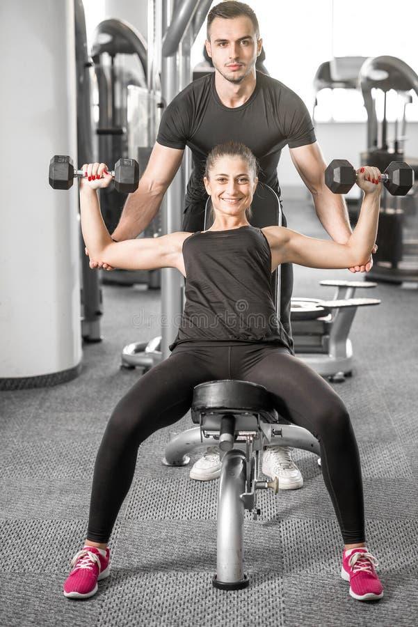 Vrouw die geschiktheid met persoonlijke trainerhulp doen stock fotografie