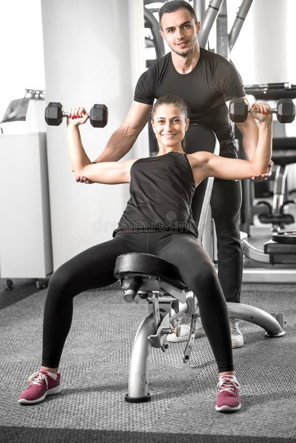 Vrouw die geschiktheid met persoonlijke trainerhulp doen royalty-vrije stock fotografie