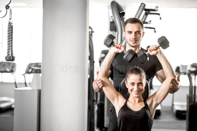 Vrouw die geschiktheid met persoonlijke trainerhulp doen stock foto