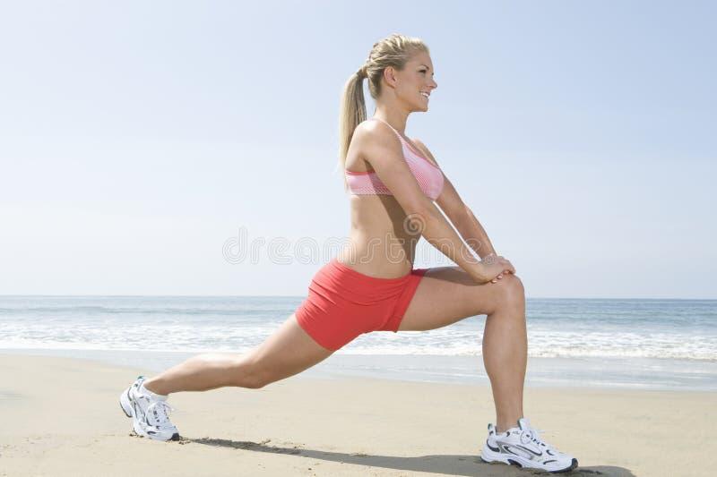 Vrouw die Geschiktheidsoefening op Strand doen stock afbeeldingen