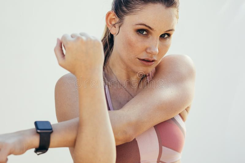 Vrouw die in geschiktheidsslijtage opwarmingsoefeningen doen Vrouwelijke atleet die training doen die een slim horloge dragen royalty-vrije stock afbeeldingen