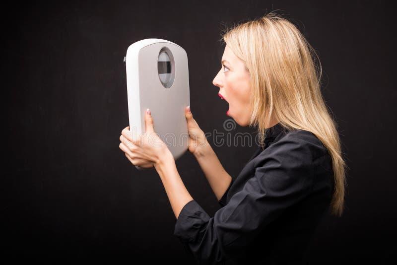 Vrouw die gewichtsschaal bekijken in schok stock afbeelding