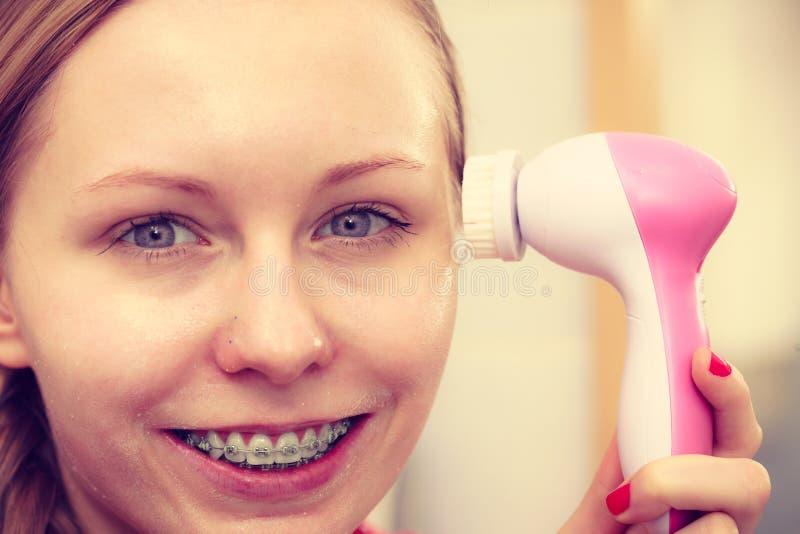 Vrouw die gezichts reinigende borstel op gezicht gebruiken stock foto